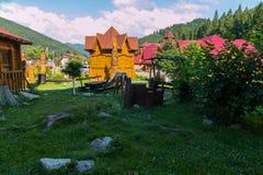 Деревянные столы с стульями с оленем вычисляют мирно пасти между ими на зеленой лужайке против фона  Стоковые Изображения RF