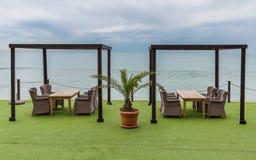 Деревянные столы и плетеные стулья обозревая море и рай ладонь Стоковое Фото
