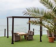 Деревянные столы и плетеные стулья под морем сени обозревая Стоковые Изображения RF