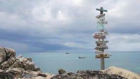 Деревянные стрелки столба знака указывая к различным городам и направлениям против вида на море с шлюпкой рыболова на предпосылке видеоматериал
