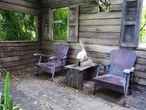 Деревянные стулья в старом доме с падать выходят на пол стоковые изображения rf