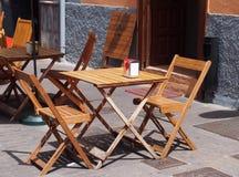 Деревянные стулья и таблицы вне кафа улицы стоковые изображения
