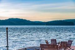 Деревянные стулья на доке который сторона озера стоковые фотографии rf