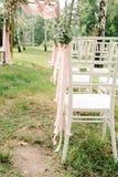 Деревянные стулья на свадьбе Стулья украшенные с петлицами и лентами для гостей стоковое фото