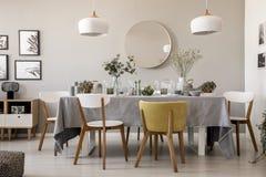 Деревянные стулья на таблице с tableware в интерьере столовой с лампами и круглым зеркалом стоковые фотографии rf
