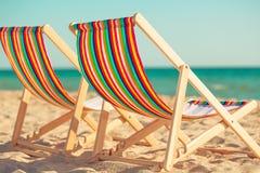Деревянные стулья шезлонга на песчаном пляже Стоковое Изображение RF