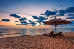 Деревянные стулья и зонтики на пляже песка Стоковые Фото