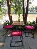 Деревянные таблица и стулья с красным валиком под деревом с солнцем освещают в мирном красивом саде рекой на задворк ресторана, S стоковые фотографии rf