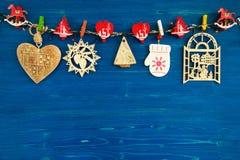 Деревянные украшения рождества и света рождества на голубой деревянной предпосылке Стоковые Фотографии RF