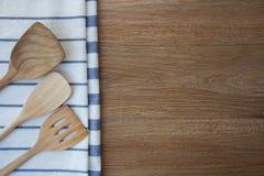 Деревянные утвари кухни и linen полотенца кухни на темных деревянных животиках Стоковое Фото