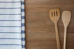 Деревянные утвари кухни и linen полотенца кухни на темных деревянных животиках Стоковая Фотография