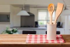 Деревянные утвари кухни на таблице с скатертью над внутренней предпосылкой с космосом экземпляра для монтажа продукта стоковая фотография rf