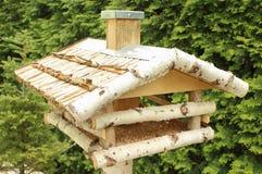 Деревянные фидер и семена птицы на зеленой предпосылке Стоковое фото RF