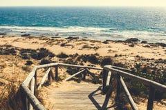 Деревянные шаги над дюнами к пляжу на накидке Trafalgar, Испании стоковые изображения rf