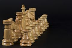 Деревянные шахматные фигуры на черной предпосылке Стоковые Изображения