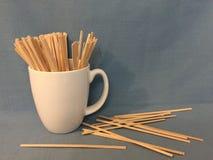 Деревянные шевелилки кофе в кружке кофе стоковые фотографии rf