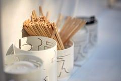 Деревянные шевелилки питья в держателе на таблице Стоковое фото RF
