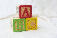 Деревянные штабелированные блоки алфавита на лоскутном одеяле говоря ABC по буквам Стоковое фото RF