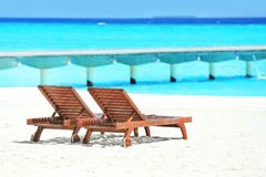 Деревянные loungers солнца на пляже моря Стоковая Фотография