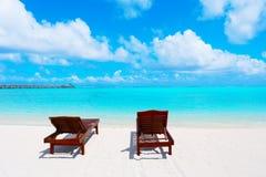Деревянные loungers солнца на пляже моря Стоковое Изображение