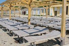 Деревянные loungers солнца на pebbled общественном пляже морем взгляд со стороны конца-вверх Стоковое Изображение RF