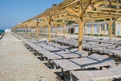 Деревянные loungers солнца на pebbled общественном пляже морем Взгляд со стороны Стоковая Фотография