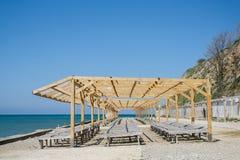 Деревянные loungers солнца на pebbled общественном пляже морем Стоковое Изображение RF