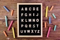 Деревянный английский алфавит ОТ НАЧАЛА ДО КОНЦА на классн классном мел на деревянных животиках Стоковые Фотографии RF