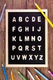 Деревянный английский алфавит ОТ НАЧАЛА ДО КОНЦА на классн классном Карандаш цвета на wo Стоковое Изображение RF
