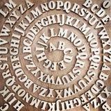 Деревянный алфавит переплел как спираль на деревянной предпосылке стоковая фотография rf