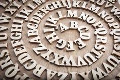 Деревянный алфавит переплел как спираль на деревянной предпосылке стоковые изображения