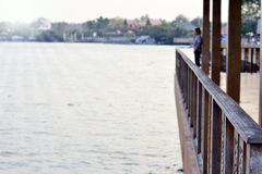 Деревянный балкон или деревянная терраса около реки с солнечным светом Стоковая Фотография