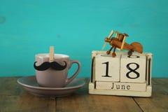 Деревянный винтажный календарь восемнадцатое -го июнь рядом с чашкой кофе и усиком стоковые фотографии rf