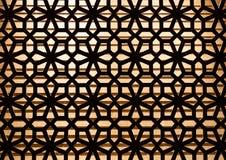 Деревянный высеките украшение картины на стене с освещением в предпосылке стоковая фотография