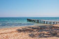 Деревянный день морской воды бирюзы пристани солнечный, камни приставает к берегу, остров Греции Романтичное одичалое место Ясное стоковое фото rf