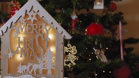 Деревянный дизайн шпаргалки с сообщением веселого рождества перед освещенным деревом акции видеоматериалы