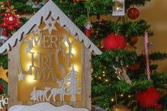 Деревянный дизайн шпаргалки с сообщением веселого рождества перед освещенным деревом стоковые фотографии rf