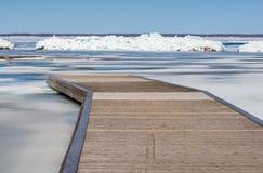Деревянный док и стена пролома на замороженном озере Стоковая Фотография