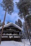 Деревянный дом в покрытом снег лесе в области Лапландии Стоковые Изображения RF