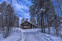 Деревянный дом в покрытом снег лесе в области Лапландии Стоковое фото RF