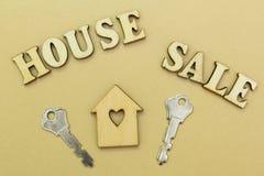"""Деревянный дом и 2 ключа, дом продажи надписи """" стоковое фото"""