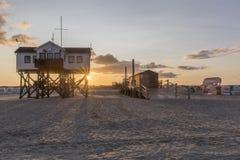 Деревянный дом на ходулях на пляже на восходе солнца Стоковое фото RF