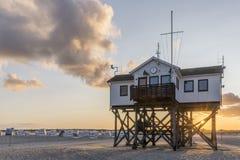 Деревянный дом на ходулях на пляже на восходе солнца Стоковые Изображения