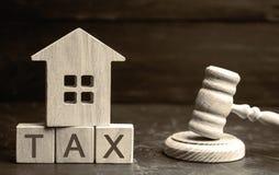 Деревянный дом с ` налога ` надписи и ` s судьи бьют молотком Налоги на недвижимости, оплате Штраф, недоимки Регистр taxpa стоковые изображения