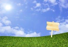 Деревянный знак на зеленом поле под голубым небом Стоковые Изображения