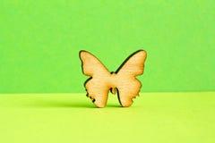 Деревянный значок бабочки на зеленой предпосылке Стоковые Фото