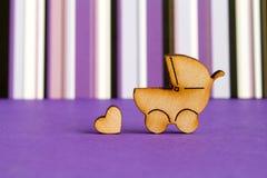 Деревянный значок striped детской дорожной коляски и меньшего сердца на пурпуре Стоковые Фото