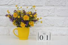Деревянный календарь 1-ое июля кубов и желтая чашка с яркими покрашенными цветками против белой кирпичной стены Дата календаря ша стоковое фото rf