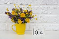 Деревянный календарь 4-ое июля кубов и желтая чашка с яркими покрашенными цветками против белой кирпичной стены Дата календаря ша стоковая фотография
