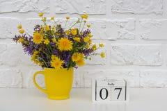Деревянный календарь 7-ое июля кубов и желтая чашка с яркими покрашенными цветками против белой кирпичной стены Дата календаря ша стоковые фото